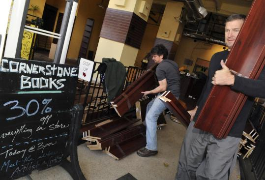 David Blake (left) and Jim McIsaac remove pieces of bookshelves after the closing of Cornerstone Books in Salem earlier this month.