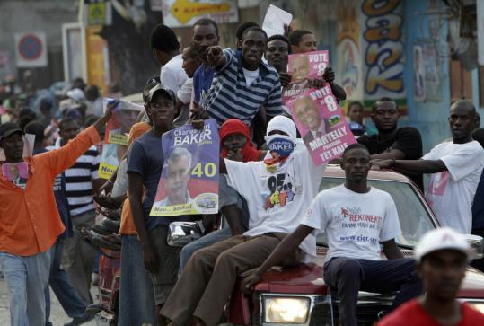Supporters of two of Haiti's 19 presidential candidates, Michel Martelly and Charles-Henri Baker, rode a pickup during a demonstration against the general elections in Port-au-Prince.