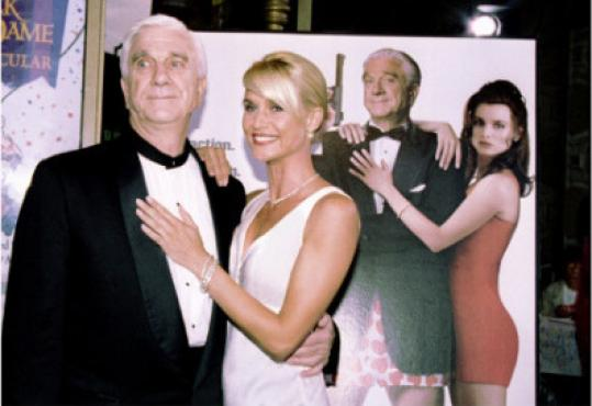"Leslie Nielsen and Nicollette Sheridan posed near a ""Spy Hard"" poster at the film's premiere."