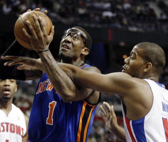 Amar'e Stoudemire of the Knicks is fouled en route to the basket by Detroit's Greg Monroe during the first half of New York's double-overtime win.
