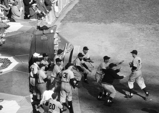 Gil McDougald was welcomed by teammates after belting a grand slam in a 13-1 rout of the Giants in Game 5 of the 1951 World Series. The Yankees won the series in six games.