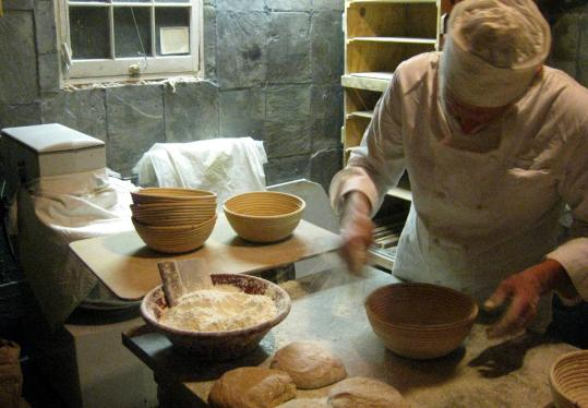 The baker works at night to make his boules, batards, and family loaves, which his wife sells at farmers' markets and to local shops.