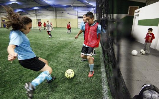 Esmeralda Hernandez tries to beat an opponent to the ball during a street soccer program in North Andover recently.