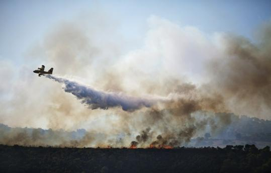 A Canadair firefighter plane sprayed water over flames in Carmel Forest on the outskirts of Haifa yesterday as thousands of Israeli firefighters and rescuers fought to control the blaze.
