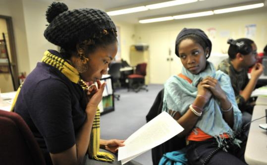 Education specialist Shauna Rigaud (left) proofread an essay by Ashley Cooper, 17, of Roxbury (second right), at a program that helps high school students prepare their college applications.