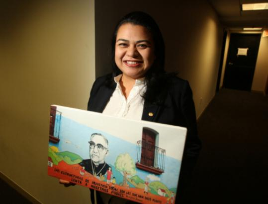 Ena Úrsula Peña with a picture of Archbishop Óscar Romero, who was murdered in 1980.