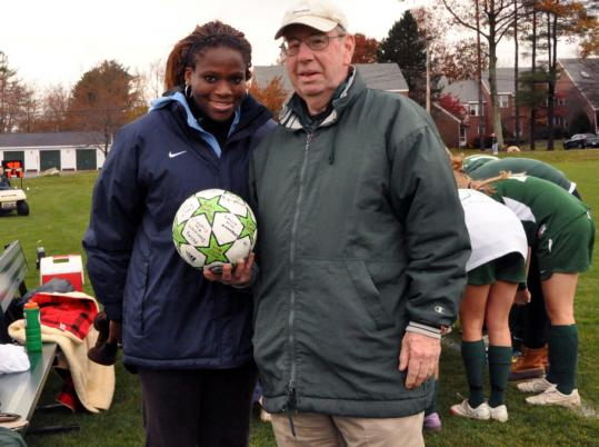 Brooks School soccer coach Bob Morahan, with assistant coach and former star player Jaime Gilbert, received a ball signed by the girls on his team.