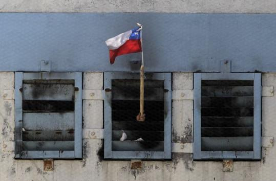 An inmate waved a Chilean flag from inside San Miguel public prison in Santiago yesterday after a fire broke out.