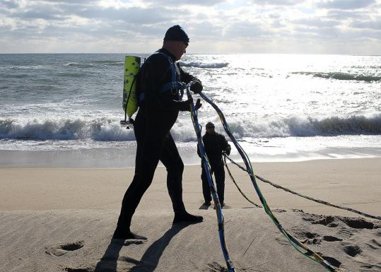 A diver checked his gear before heading into the sea yesterday to plant a device that monitors water currents.