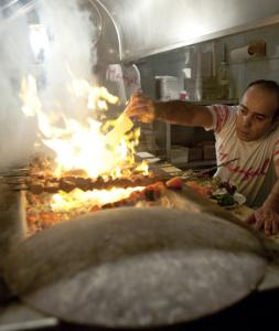 The cook sits by the charcoal pit at Mangal 1, a Turkish barbecue restaurant in London.