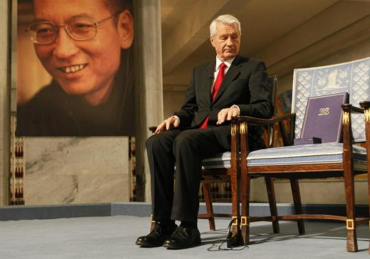 Torbjorn Jagland, the Nobel committee's chairman, looked at the Peace Prize medal and certificate that he hoped to hand to Chinese dissident and intellectual Liu Xiaobo but instead placed on an empty chair. A portrait of Liu is seen in the background.