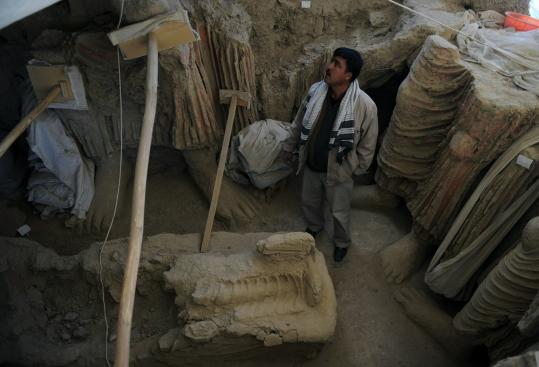 An archaeologist looks at Buddha statues discovered in an ancient monastery in Afghanistan. An informal agreement has allowed three years to finish excavations at the site before a Chinese company begins work on a huge unexploited copper mine.