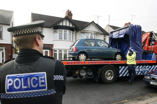A police officer watched as a car was removed from outside the house in Luton, England, searched yesterday by British police.