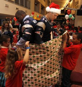 Young fans wrap Patriots players Vince Wilfork and Zoltan Mesko at Gillette Stadium yesterday.