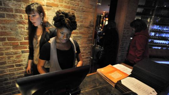 Cori Simeon-Ohiri and co-worker Sara Silberstein (left) are hostesses at Scampo in Boston. Simeon-Ohiri was hired in November after a three-month job search.