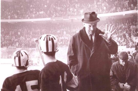 An archival photo shows Ed Burns coaching Arlington High's hockey team, a 50-year legacy that included 695 wins.