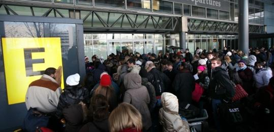 Passengers lined up at Heathrow Airport's Terminal 3 yesterday, as severe weather caused flight delays and cancellations.