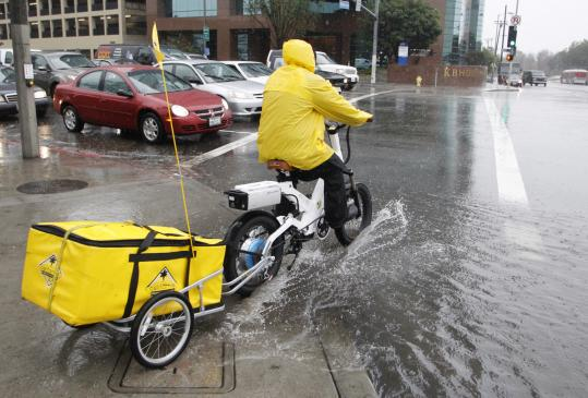 A restaurant bike delivery man crossed through a flooded corner on Wilshire Boulevard in Los Angeles yesterday.