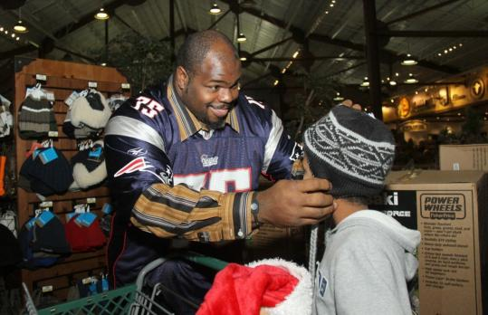 Vince Wilfork helps a young friend during a shopping spree recently at Bass Pro Shops at Patriot Place.