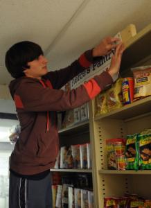 Pierce Keegan restocks the Acton Food Pantry's gluten-free offerings recently.
