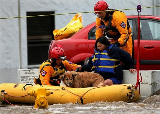 Linda Dealy and her dog were rescued yesterday after being stranded in the Premiere Hotel when flood water rose during a powerful rainstorm in San Diego.