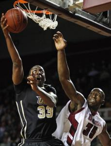 Central Florida's Keith Clanton dips under the rim and drops home a basket despite the long-arm defense of Hashim Bailey.