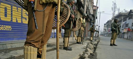 Indian Central Reserve Police Force soldiers stand guard during a curfew in Srinagar, the summer capital of Kashmir .