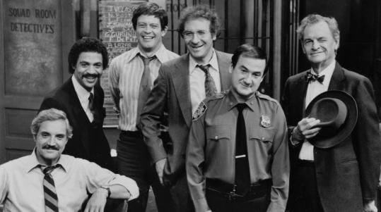 "Steve Landesberg (center, with glasses) with the cast of ""Barney Miller,'' including (from left) Hal Linden in the title role, Ron Glass, Max Gail, Ron Carey, and James Gregory."