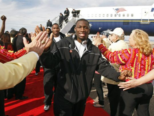 Running back Jordan Todman and his UConn teammates are greeted after arriving in Phoenix to play in the Fiesta Bowl.