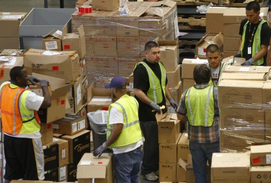 Workers unloaded merchandise at an Amazon.com facility in Phoenix. Up to 30 percent of purchases from e-retailing companies are returned; Amazon has developed technology to allow users to prevent items bought as gifts from being mailed.
