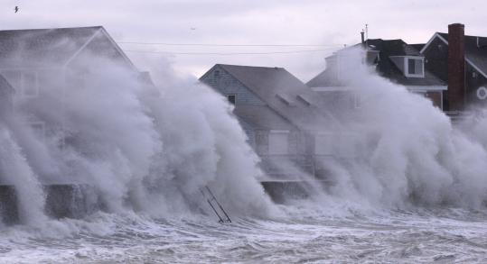 SCITUATE &#8212; Waves crashed into homes along Oceanside Drive yesterday afternoon. The area saw flooding and fires earlier in the day.