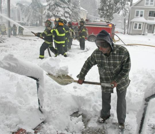 In Brockton, Manny Dossantos shoveled his front sidewalk yesterday while firefighters battled a blaze at his neighbor's house. Dossantos discovered the fire at 261 West Elm St. just after 7 a.m., when he heard glass breaking and crackling and called 911. There were apparently no residents at home at the time, and no injuries were reported.