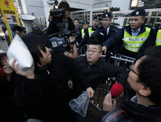 A protester aimed a bag of milk powder at a government liaison office during a demonstration in Hong Kong yesterday.