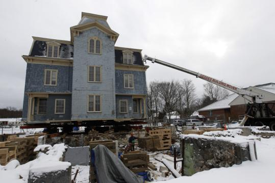 Employees of Geddes Building Movers of Bow, N.H., prepared to move the 136-year-old Colburn School building so that a new town library can be built in its place in Westwood.