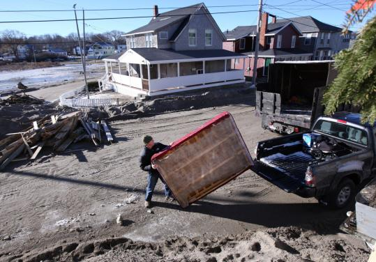 Greg Griffin helped a friend move belongings out of a storm-damaged home on Oceanside Drive in Scituate on Tuesday.