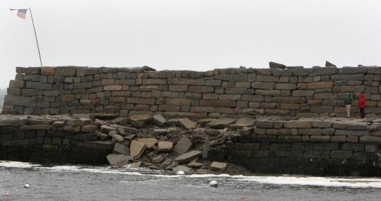 Strong ocean surges took out a roughly 30-foot section (above) of the north side of the sea wall in Gloucester's Lanes Cove and knocked down three rows of granite blocks on the wall's south side. The damage could cost $1 million to repair.