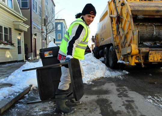 Trash collector Vladimir Diaz removed an old table being used to reserve a shoveled parking space yesterday on East Third Street in South Boston.