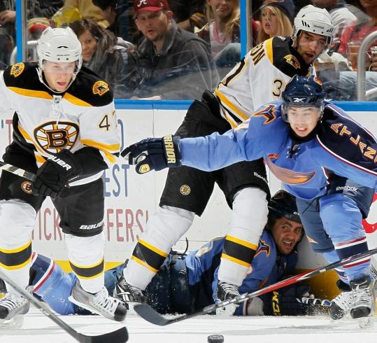 Bruins defenseman Steven Kampfer (left) appears to have the jump on the Thrashers' Tim Stapleton in a chase for a loose puck.
