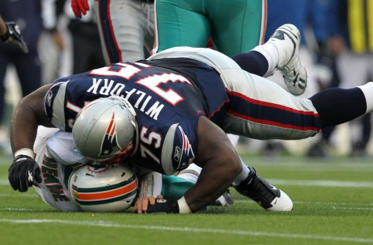 Vince Wilfork flattens Miami's Chad Henne — and earns a flag for a helmet-to-helmet hit.
