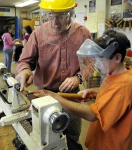 Ben Kellman, woodshop instructor at Marshall Middle School in Billerica, gives Nick Barbas pointers on wood lathe technique.