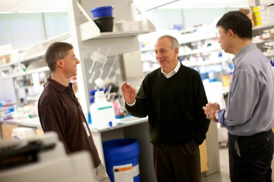 Dr. Mark Fishman (center) spoke with drug researchers at Novartis in Cambridge.