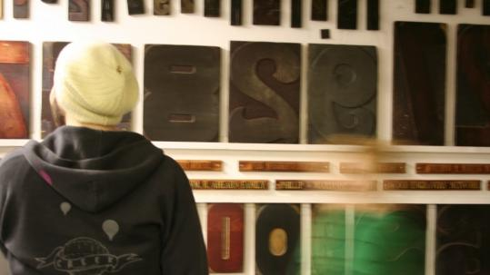 """A printmaker looks at a wall of woodblock letters in the new film """"Typeface.''"""