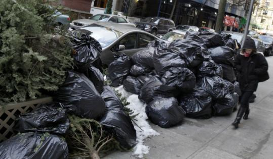 Trash remained piled in New York yesterday as the city braced for more snow. Storm cleanup had delayed trash pickup.