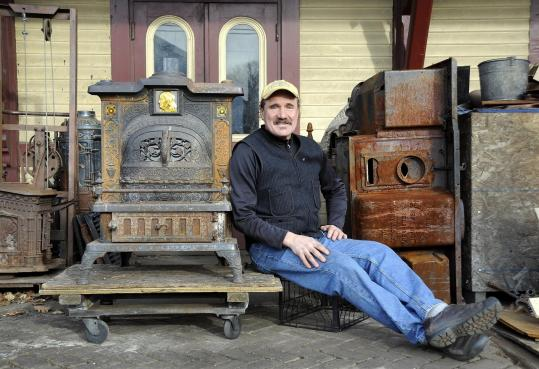 David Erickson takes old stoves, such as the 1885 Ivy Franklin to his right, and breathes new life into them at his shop in a former Littleton train depot.