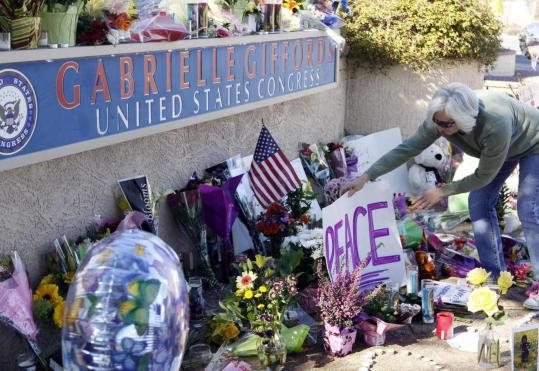 A woman tended a memorial yesterday outside the Tucson office of Representative Gabrielle Giffords, who was shot Saturday.