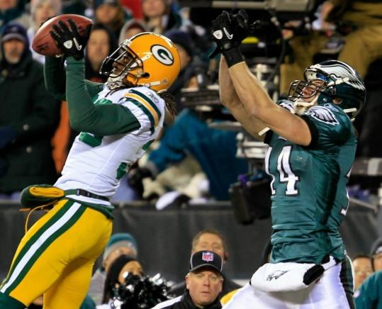 Packers cornerback Tramon Williams intercepts a pass intended for the Eagles' Riley Cooper in the end zone with 33 seconds left.
