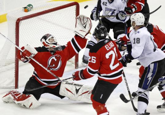 With traffic in front, Devils goalie Martin Brodeur reaches out with his glove to make one of his 33 saves against the Lightning.
