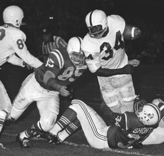 Buffalo's Cookie Gilchrist tried to bull past Patriots Nick Buoniconti and Chuck Shonta in 1962.
