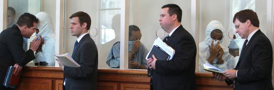With lawyers at the ready, Marvin Veiga (in hospital gown) and codefendants Osvaldir Mendes (left), Daronde Bethea, and (partially hidden) Takari Elliott, were arraigned on firearms and other charges yesterday in Dorchester. Veiga is accused of pointing an assault rifle at police after a high-speed chase Saturday.