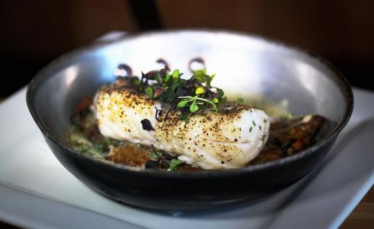 Roasted cod, served in the skillet, sits atop a potato-scallion pancake in a shallot cream sauce.